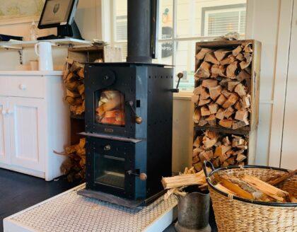 Freestanding Woodburner fireplace in Restaurant interior with wood storage