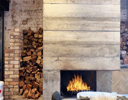 Corner Open wood fireplace in grey concrete surround in a restaurant interior